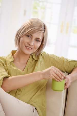 Portrait of young blonde woman sitting on couch at home, drinking tea, looking at camera smiling. Stock Photo - 8747904