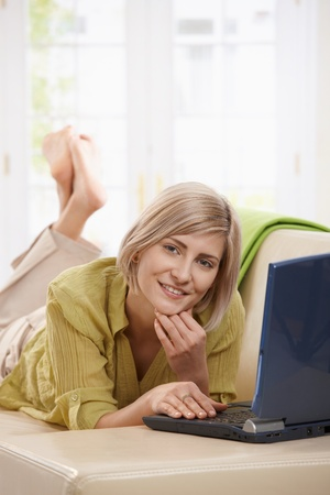 lying in front: Attractive woman lying on living room couch using laptop, looking at camera, smiling.  Stock Photo
