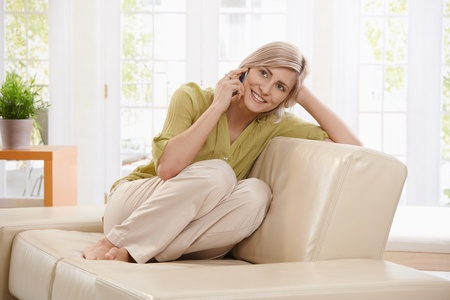 Beautiful blonde woman on call sitting on living room sofa with legs pulled up, smiling.