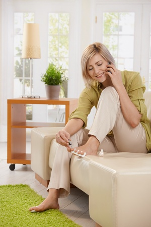 Smiling woman talking on mobile phone while using nail polish on toes sitting on couch at home. photo