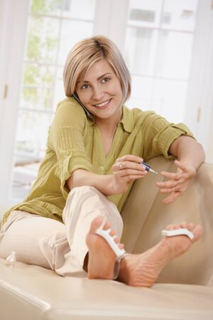 Smiling woman using nail polish on hands sitting with feet up on sofa talking on phone  in living room. Stock Photo - 8747838