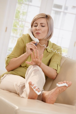 Woman sitting on couch drying nail polish on hand, listening to phone call. photo