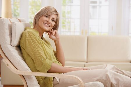 cosy: Portrait of mid-adult woman smiling at camera sitting in armchair in bright living room with hand up at face.