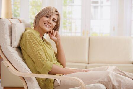 BUEN VIVIR: Retrato de mid-adult mujer sonriendo a la c�mara que sentarse en el sill�n en el Sal�n brillante con la mano en la cara. Foto de archivo