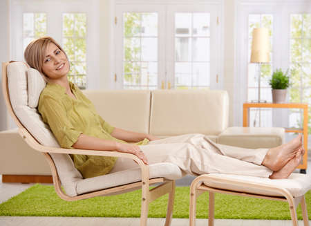 feet up: Woman relaxing at home, sitting in armchair with crossed feet up on footboard, smiling at camera. Stock Photo