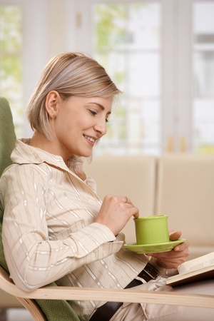 Woman sitting in armchair, reading book, holding coffee mug, smiling. photo