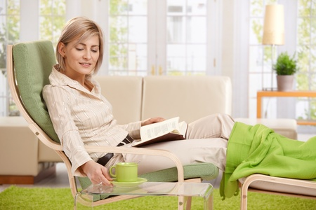 Woman relaxing in armchair at home, reading book with feet up, putting coffee on table, smiling. photo
