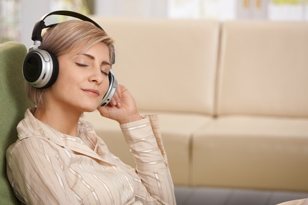 Portrait of smiling woman sitting with eyes closed listening to music on headset. photo