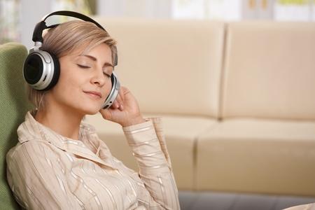 escuchando musica: Retrato de mujer sonriente sentado con los ojos cerrados escuchando música en el auricular. Foto de archivo