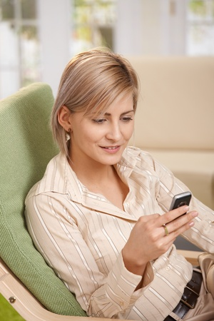 Smiling blonde woman sitting in armchair at home, using mobile phone, having coffee mug on table. photo