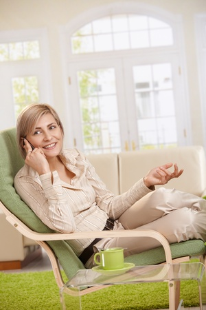 recreation room: Cheerful woman speaking on cellphone sitting in living room armchair.