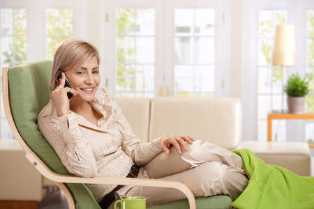 Cheerful woman speaking on cellphone sitting in living room armchair. photo