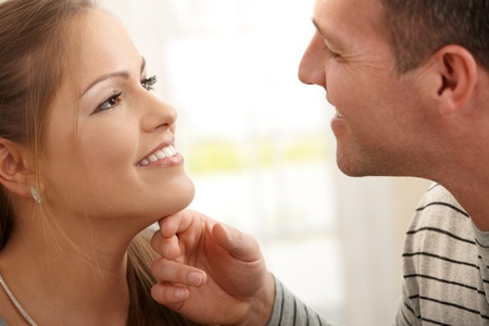 Loving couple smiling at each other, man stroking womans neck. photo