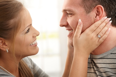 Portrait of smiling couple's faces in closeup, woman holding man's face in both hands. Stock Photo - 8747974