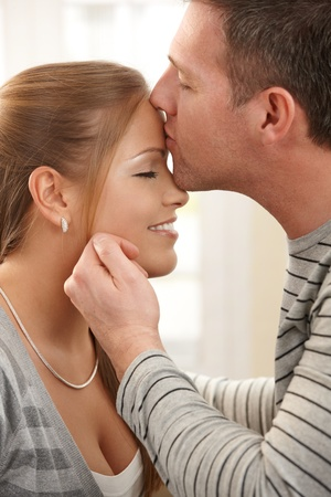 hand on forehead: Portrait of happy couple in love, man kissing woman on forehead, stroking face with eyes closed. Stock Photo