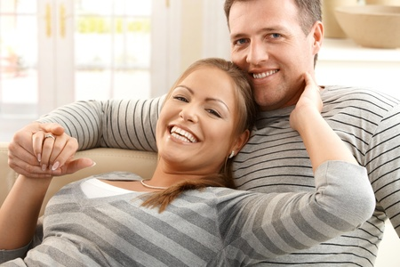 Happy couple laughing together, lookign at camera, sitting on sofa at home holding hands. Stock Photo - 8748001