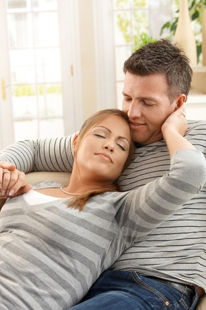 at each other: Happy couple holding each other sitting on sofa with eyes closed at home.