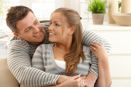 each: Mid-adult couple looking at each other hugging in living room, smiling.