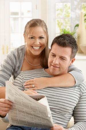 amigos abrazandose: La sonriente pareja junto en la sesi�n de lectura peri�dico sala, abrazos.