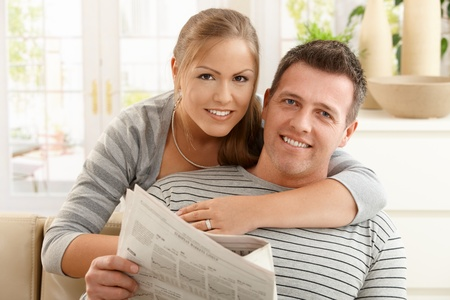 news room: Smiling couple reading newspaper together in sitting room, hugging.