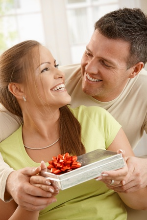 Couple sitting together laughing happily, woman holding present, man holding woman's hands. Stock Photo - 8747983