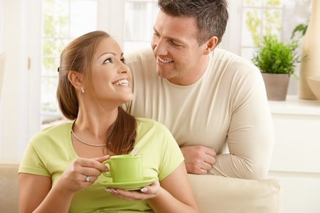 green clothes: Happy couple sitting in living room, woman holding tea cup with two hands looking up at man smiling.