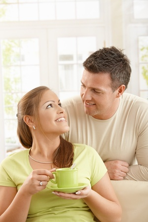 Happy couple sitting in living room, woman holding tea cup with two hands looking up at man smiling. Stock Photo - 8747906