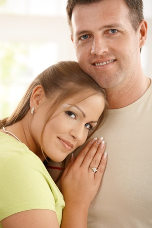 Portrait of content couple looking at camera, woman leaning on mans chest, smiling. photo