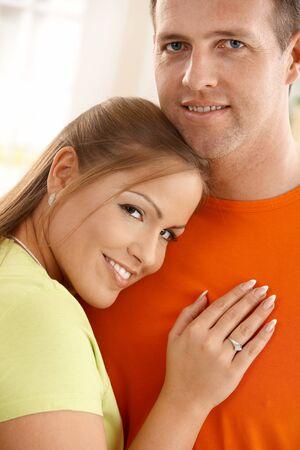 hombros: Retrato de mid-adult par sonriendo, cabeza de mujer inclinada sobre el hombro del hombre, de la mano en el pecho.