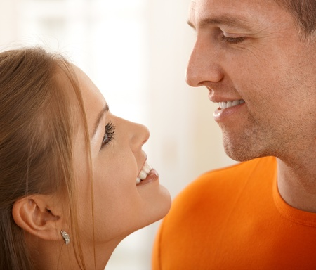 Smiling faces of loving couple looking at each other in closeup. photo
