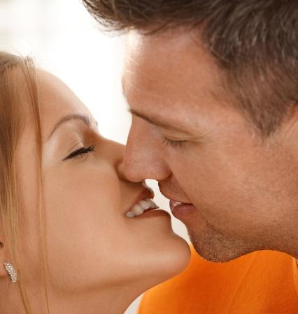 novios besandose: Hombre besos a mujer sonriente en detalle, los ojos cerrados. Foto de archivo