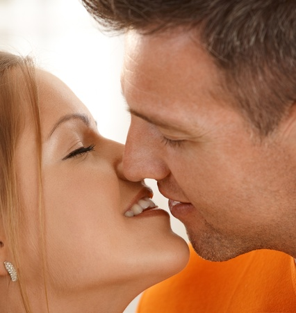 love kissing: Man kissing smiling woman in closeup, eyes closed.
