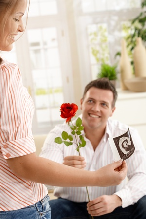 Smiling mum holding ultrasound image of baby, dad giving red rose smiling, sitting on couch. Stock Photo - 8747792
