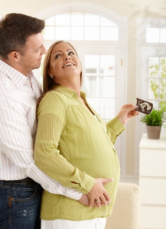 Happy couple expecting baby  looking at each other laughing, holding ultrasound photo of baby standing in living room. Stock Photo - 8747924