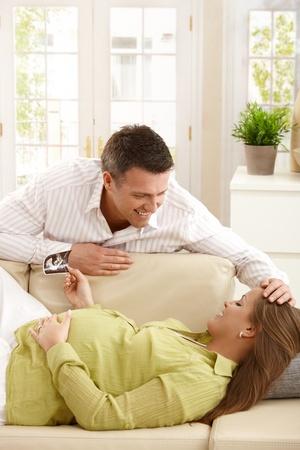부모 기대 아기, 엄마가 그녀의 머리를 행복하게 쓰다듬어 초음파 그림을 들고 소파에 누워, 스톡 콘텐츠