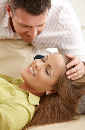 Smiling man stroking happy woman's hair lying with eyes closed on sofa. Stock Photo - 8747958
