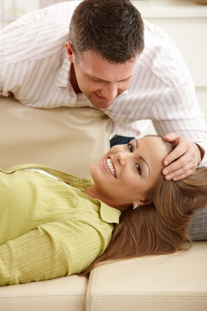Happy woman lying on sofa smiling, man stroking womans hair leaning close. photo