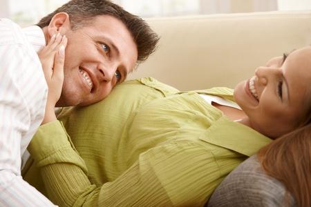 homme enceinte: Femme enceinte gisant sur le canap�, souriant, man, �couter les pulsations du b�b� t�te sur le ventre. Banque d'images