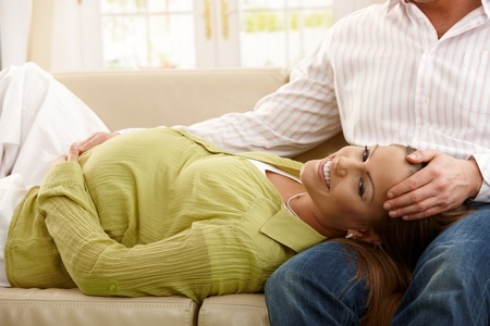 Happy pregnant woman lying on sofa in man's lap, man holding her head. Stock Photo - 8747976