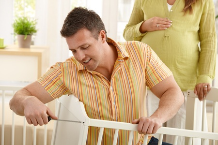 Dad fixing baby's bed at home, pregnant mum in background. Stock Photo - 8747925