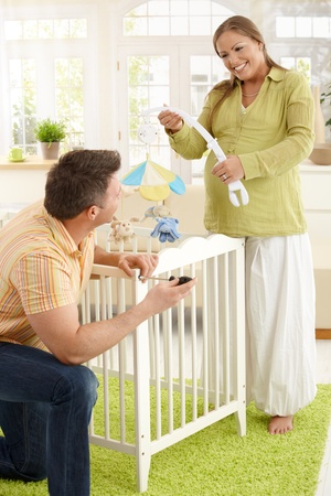 Happy couple expecting baby putting baby bed together in living room, laughing. photo