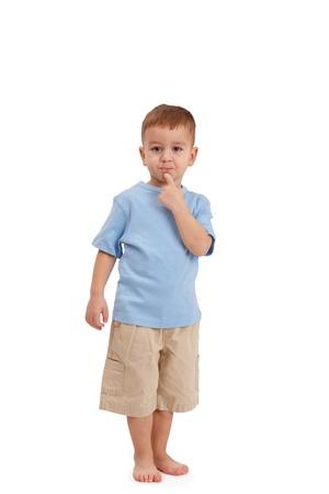 Little boy posando, tirando de la cara, mirando la cámara en el estudio.