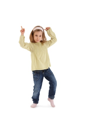 Sweet little girl posing in studio, dancing, pointing, concentrating. photo