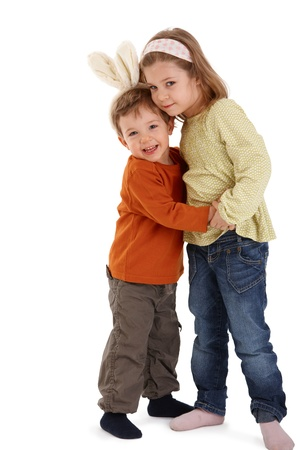 Cute kids hugging, smiling at camera, little boy wearing funny bunny hair band. photo