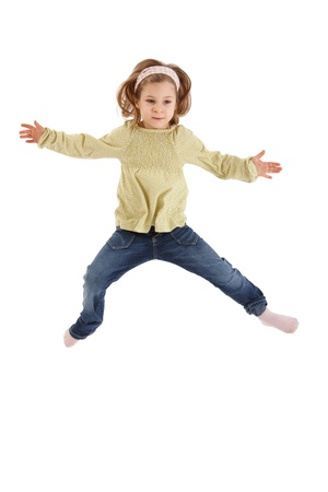 Little girl jumping with arms wide open, smiling. photo
