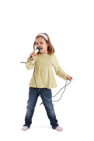 Cute little girl playing with microphone, singing. photo