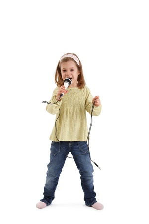 Little girl singing with microphone in studio. photo