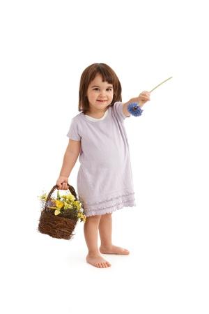 Cute girl in sweet dress handing blue flower, holding basket full of spring flowers, smiling. photo