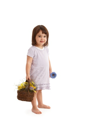 Sweet girl with basket full of spring flowers, smiling at camera. photo
