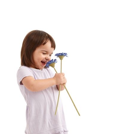 three persons only: Cute little girl laughing, smelling spring flowers.